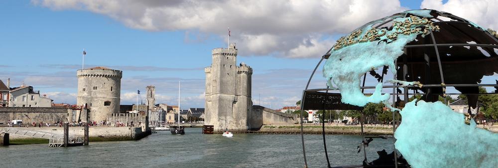 @crédit photo Mobilboard La Rochelle L'entrée du Vieux Port avec la tours Saint-Nicolas et la toir de la chaîne – Le Globe de la Francophonie